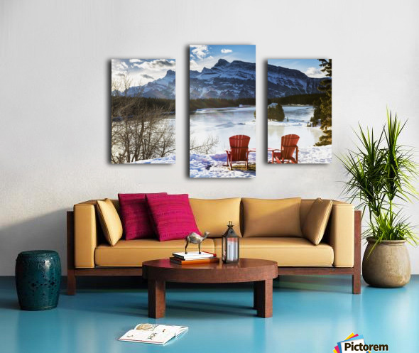 Two red chairs on snow covered ridge overlooking frozen lake with snow covered mountain in the background with blue sky and clouds; Banff, Alberta, Canada Canvas print