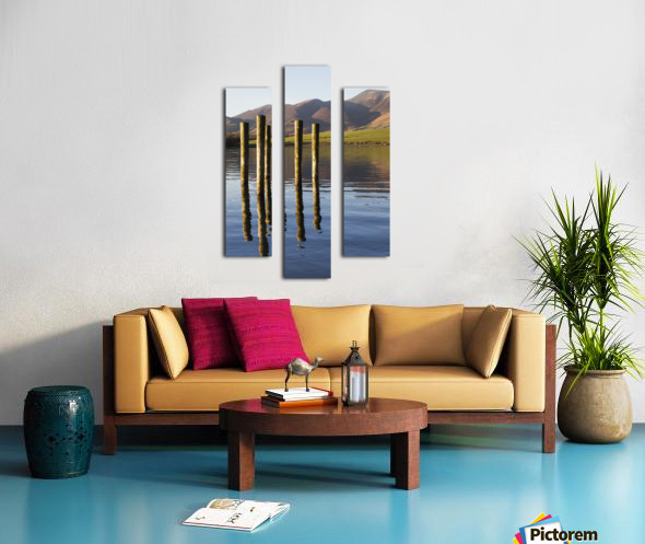 Wooden posts reflected in tranquil after with mountains the the background; Keswick, Cumbria, England Canvas print