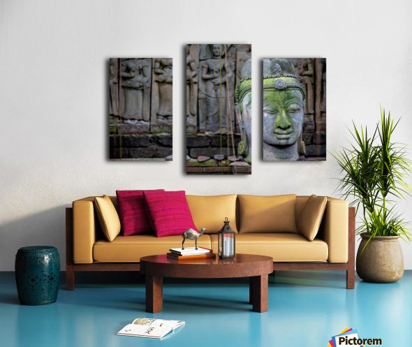 A terra cotta head of buddha sits in front of bas-relief in a terra cotta garden; Chiang Mai, Thailand Canvas print