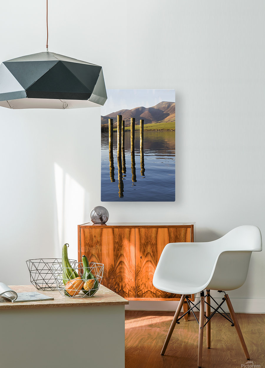 Wooden posts reflected in tranquil after with mountains the the background; Keswick, Cumbria, England  HD Metal print with Floating Frame on Back
