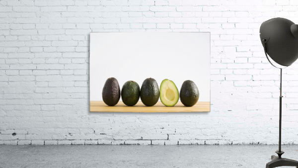 A Row Of Avocados Standing Upright On A Wooden Board With One Cut In Half Without The Pit; Calgary, Alberta, Canada