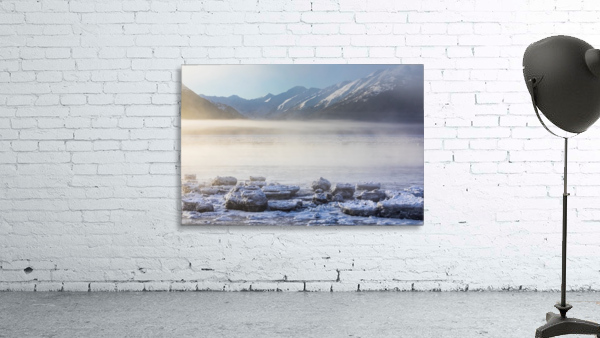 The sun shines through low altitude fog cast in warm light along Turnagain Arm and the Seward Highway, sea ice covering the ocean in the foreground, the Kenai Moutains revealed in the background, South-central Alaska; Alaska, United States of America