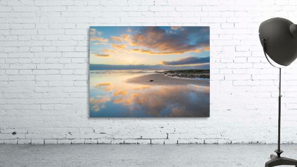Beach sunrise reflected on the wet sand