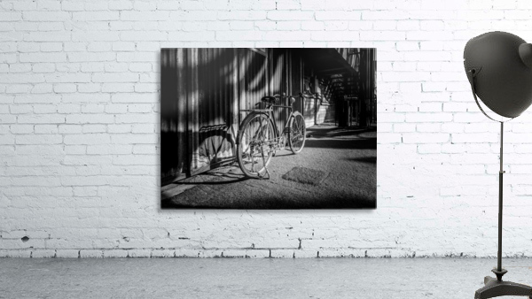 Bicycle parked against the building black and white