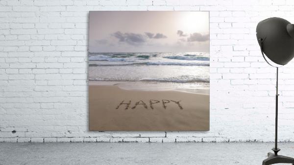Sand writing - Word Happy written on beach