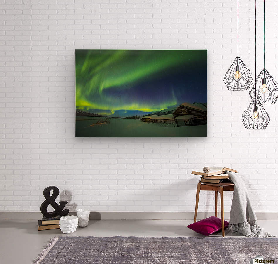 The aurora fills the sky above the historic Black Rapids Roadhouse along the Richardson Highway on a bitterly cold night; Alaska, United States of America  Wood print