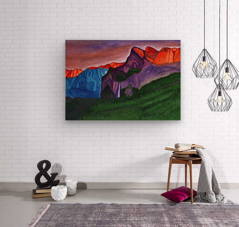 Snowy peaks of the mountains with a waterfall lit up by the orange dawn  Wood print