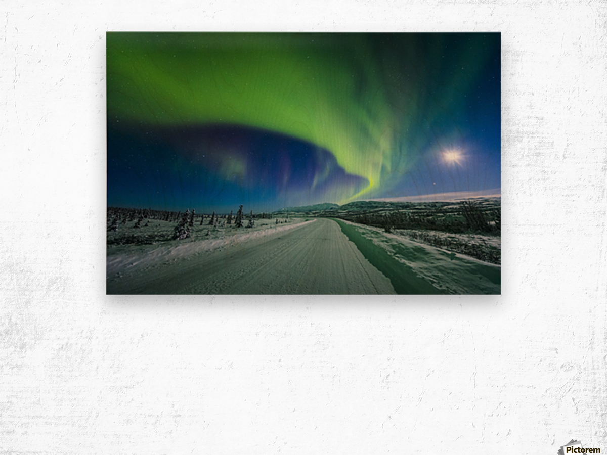 The moon and aurora shine in the night sky over a snow covered Richardson Highway south of Delta Junction; Alaska, United States of America Wood print