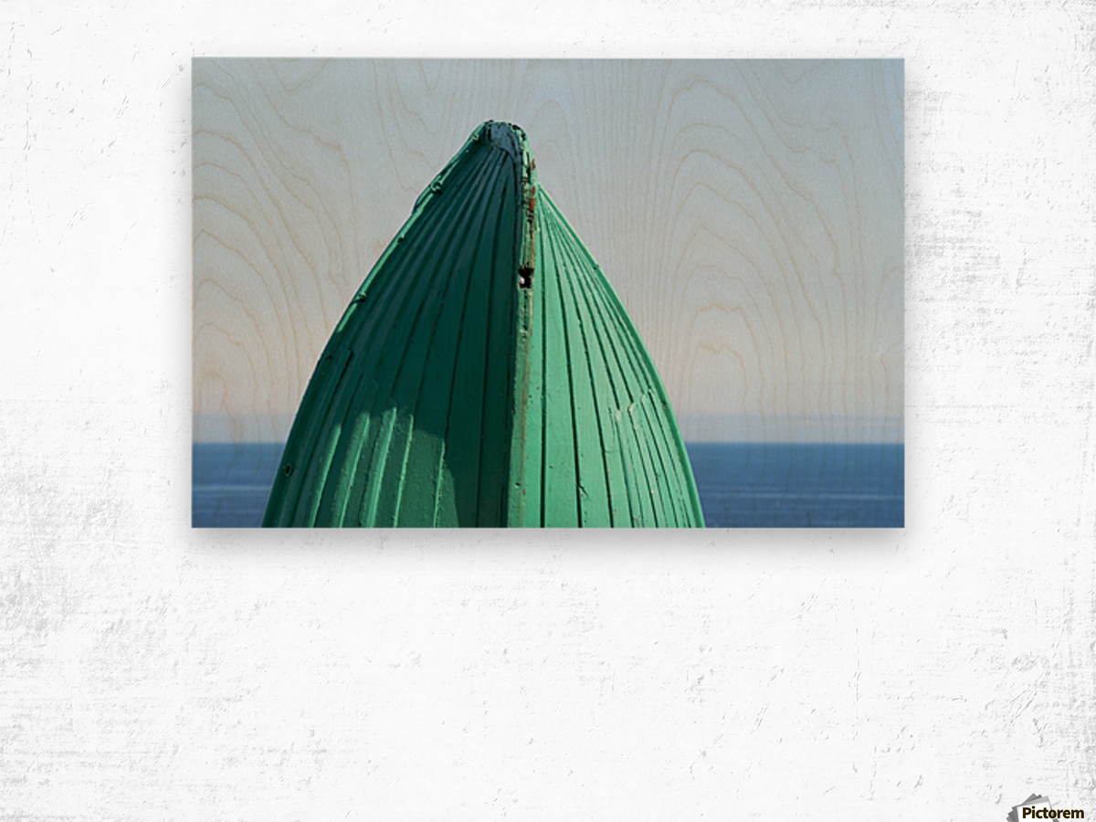 Close-up of  the bottom of the bow of a wooden boat painted green and the tranquil water and blue sky in the background; South Shields, Tyne and Wear, England Wood print
