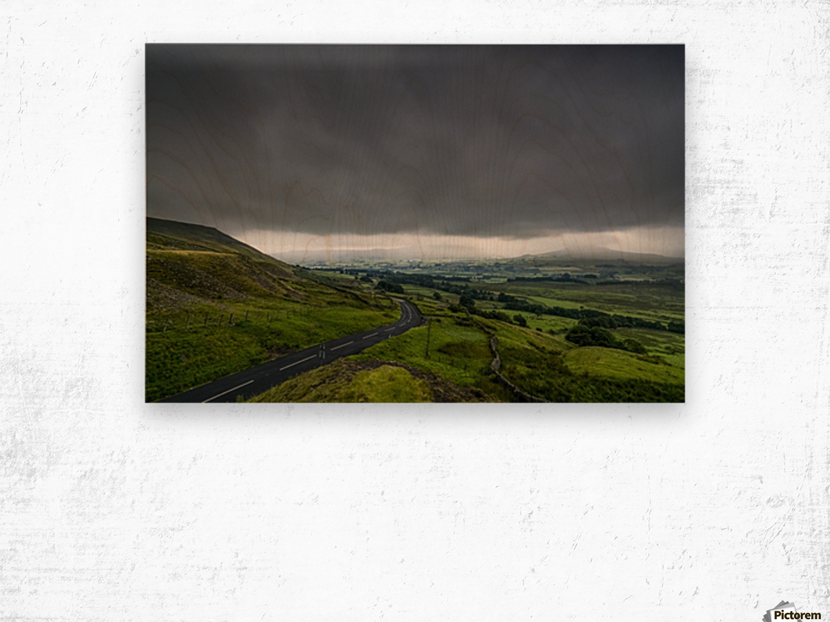 Dark storm clouds over a lush, green landscape and road; North Yorkshire, England Wood print