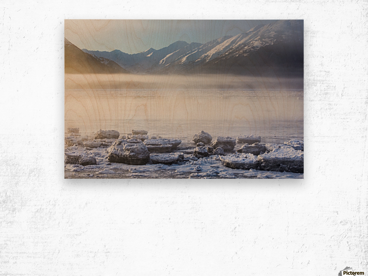 The sun shines through low altitude fog cast in warm light along Turnagain Arm and the Seward Highway, sea ice covering the ocean in the foreground, the Kenai Moutains revealed in the background, South-central Alaska; Alaska, United States of America Wood print