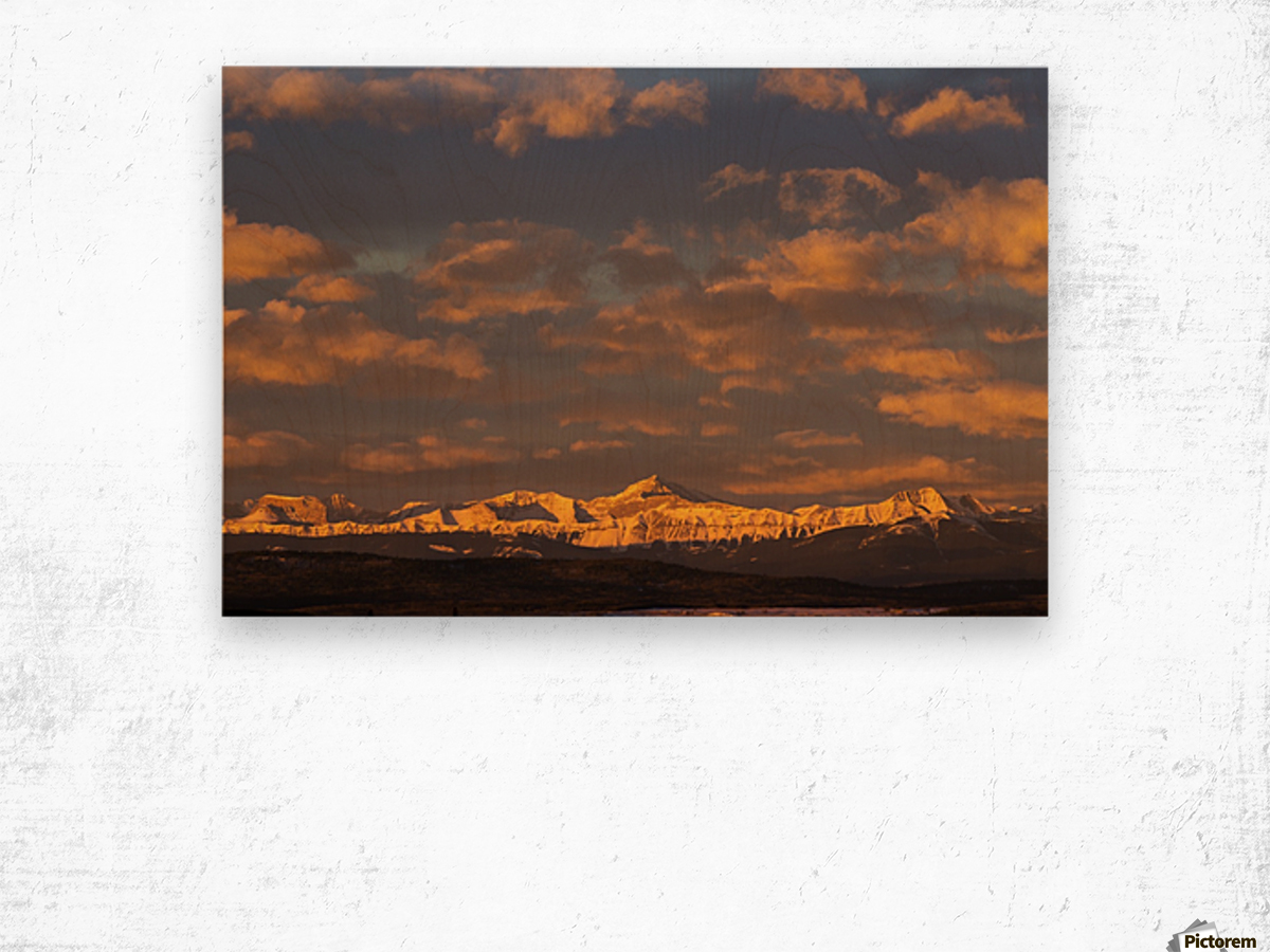 Glowing warmly lit snow covered mountain range and foothills with glowing clouds and blue sky at sunrise; Calgary, Alberta, Canada Wood print