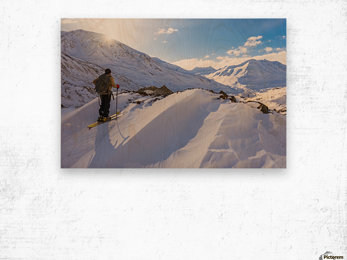A backcountry skier looks over the Black Rapids Glacier valley from a high point on the terminal moraine in winter; Alaska, United States of America Wood print