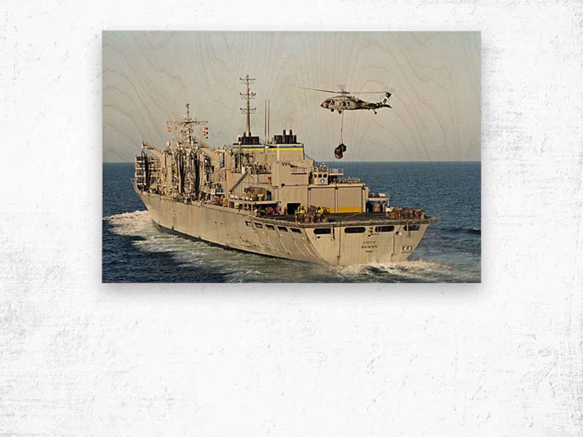 An MH-60S Knighthawk lifts cargo from the fast combat support ship USNS Rainier. Wood print