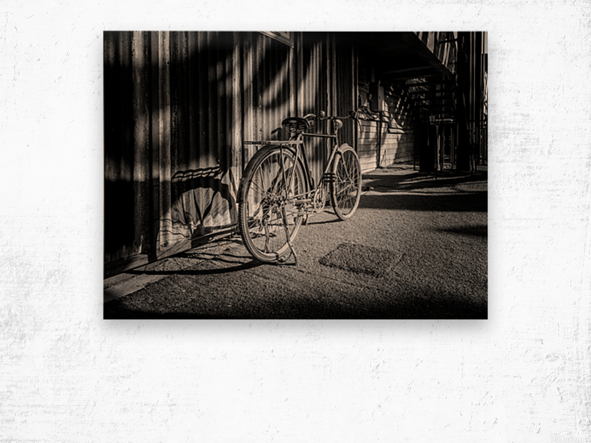 Bicycle parked against the building black and white Wood print