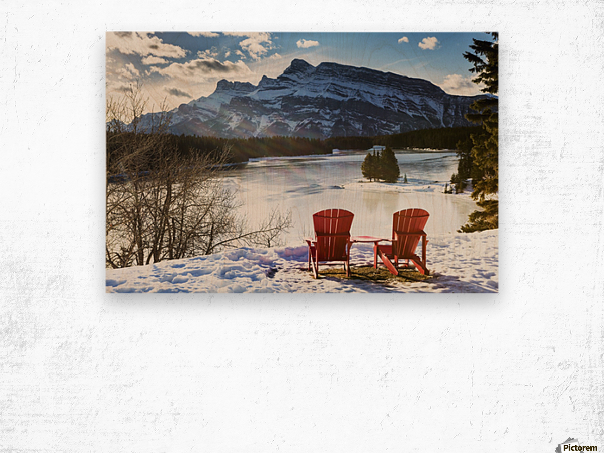 Two red chairs on snow covered ridge overlooking frozen lake with snow covered mountain in the background with blue sky and clouds; Banff, Alberta, Canada Wood print